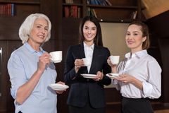Female colleagues posing during coffee break Stock Photo