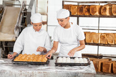 Female Colleagues Preparing Breads At Table Stock Photos