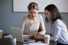 Female partners negotiating project on laptop during meeting royalty free stock images