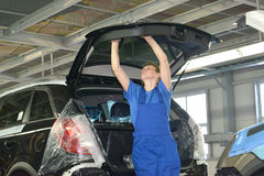 The female collector fixes a detail on a car luggage carrier doo. R. Assembly shop of automobile plant Royalty Free Stock Photo
