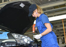 The female collector fixes a detail in podkapotny space of the c. Ar. Assembly shop of automobile plant Stock Image