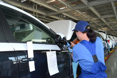 The female collector fixes a mirror on a car body by means of th. E screw gun. Assembly conveyor of automobile plant Stock Photography