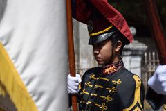 Female College military cadet on standing formation holding national flag Royalty Free Stock Photos