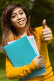 Female college student with books gesturing thumbs up in park Royalty Free Stock Image