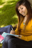 Female college student doing homework in park Royalty Free Stock Photos