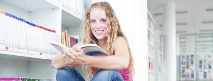 Female college student in a library. Pretty female college student in a library Royalty Free Stock Images