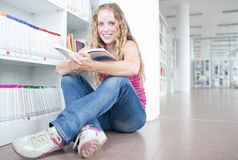 Female college student in a library. Pretty female college student in a library Royalty Free Stock Photography