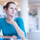 Female college student in a library. (shallow DOF; color toned image Stock Photo