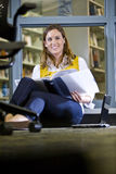 Female college student on library floor studying. Attractive young female university student sitting on library floor studying Royalty Free Stock Photo