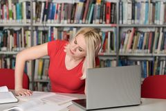Sad Female Student in the University Library. Female College Student Looks Tired While Studying With a Laptop and Textbooks in the Library stock photos