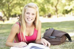 Female College Student Lying In Park Reading Textbook Stock Photos