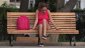 Female College Student Relaxing On Park Bench. A young Peruvian adult female stock video