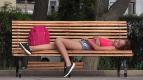 Female College Student Resting On Park Bench. A pretty young hispanic woman stock footage