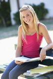 Female College Student Sitting On Bench With Book Stock Image