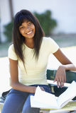 Female College Student Sitting On Bench Reading Textbook Stock Photo