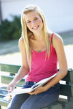 Female College Student Sitting On Bench Reading Textbook. Male College Student Sitting On Bench With Book Royalty Free Stock Photography