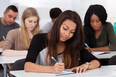 Female college student sitting in classroom. Portrait of smiling female college student sitting at desk with classmates in background Stock Photos