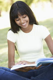 Female College Student Sitting In Park Reading Textbook Stock Images