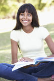 Female College Student Sitting In Park Reading Textbook Royalty Free Stock Photo