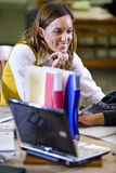 Female college student studying in school library. Pretty female university student studying at table in school library Stock Images