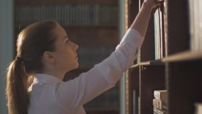 Female college student taking book from shelf in library. lead hand on the shelves with books. Female college student taking book from shelf in library. A stock video footage