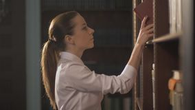 Female college student taking book from shelf in library. lead hand on the shelves with books. Female college student taking book from shelf in library. A stock footage