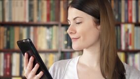 Female college student using e-book in university library. Bookcase bookshelves in the background. Smiling female college student reading e-book in university stock video footage