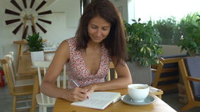 Female college student writing in notepad with pen stock video footage