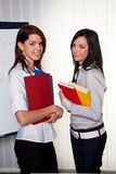 Female college students. Two smiling female college students, one holding colorful folders, the other holding colorful books, standing in a classroom setting Stock Photo