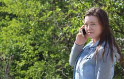 Female College/University Student Outdoors, Using Cell Phone Mobile Phone. This horizontal image shows a young woman who is a college or university student Stock Photo