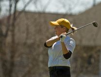 Female collegiate golfer swinging golf club Royalty Free Stock Image