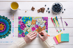 Female coloring adult coloring book, mindfulness concept. Flat lay, female coloring adult coloring books, new stress relieving trend Royalty Free Stock Photography
