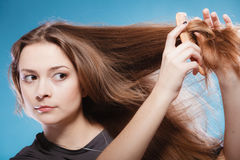 Female combing hair with wooden comb. Haircare concept. Female combing brown hair with wooden comb studio shot on blue Stock Photos