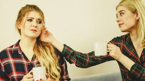 Female comforting her friend. Two women spending time together on sofa drinking tea. Female complaining, the other one comforting her. Perks of friendship Royalty Free Stock Image