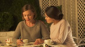 Female comforting upset sister, sitting outside on terrace and drinking coffee. Stock footage stock video