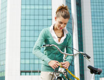 Female commuter. Locking padlock to her bike. Copy space royalty free stock image