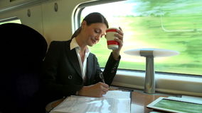 Female Commuter With Coffee On Train Working On Document stock video