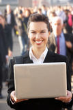 Female commuter in crowd. Using laptop royalty free stock image