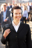 Female commuter in crowd. Wearing headphones royalty free stock photos