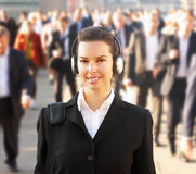 Female commuter in crowd. Wearing headphones royalty free stock photo