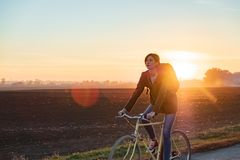 Female commuter riding a bike out of town. Woman cycling along t stock photography