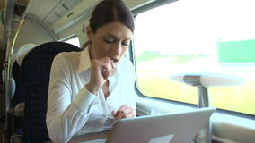Female Commuter On Train Using Laptop Whilst Eating Sandwich stock footage
