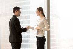 Female company secretary meeting client in office. Friendly smiling female and male business partners handshaking standing near window. Company office manager Royalty Free Stock Photo