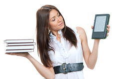 Female compare books and new wireless. Reading digital book Device. She holds books and ebook reader in hands like balance isolated over white background royalty free stock images