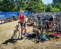 Female competitor in Ironman Triathlon race. VICTORIA, BRITISH COLUMBIA JUNE 14, 2015 Female competitor enters the bike compound after 90 km ride. The Ironman stock image