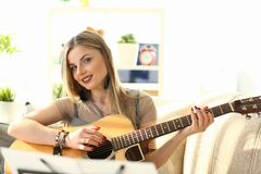 Female Composer Working on Music Create Tutorial. Woman Training Acoustic Guitar Playing while Sitting on Sofa at Home. Charming Blond Lady Looking at Camera royalty free stock photo