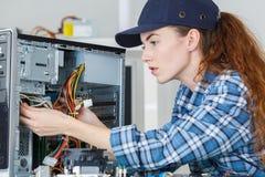 Female computer engineer repairing computer. Female Stock Photo