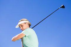Female concentrating golfer taking a shot Royalty Free Stock Photography