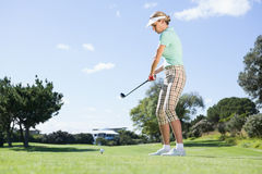 Female concentrating golfer teeing off Stock Image