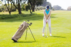 Female concentrating golfer teeing off Royalty Free Stock Photography